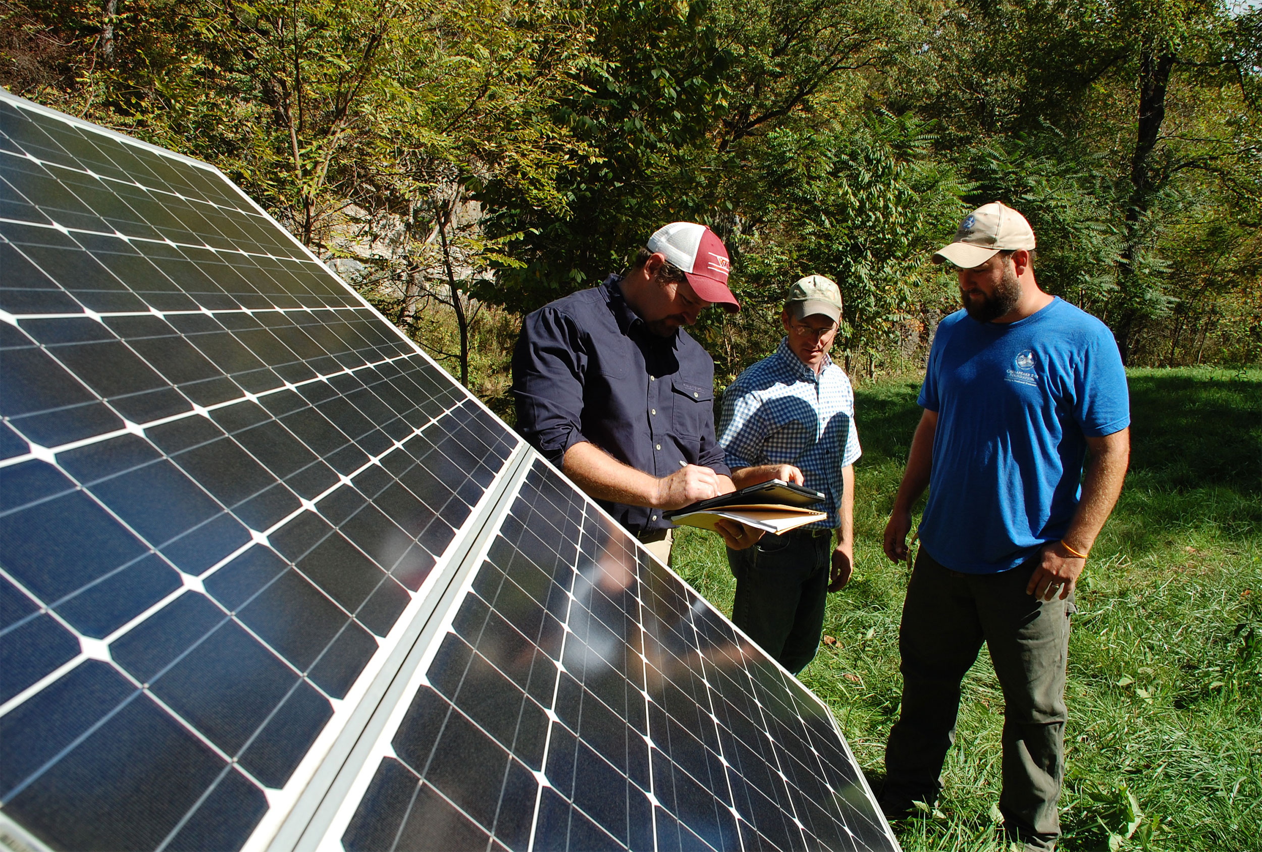 Extension Specialist John Ignosh and Extension Agent Matt Booher work with Alston Horn of the Chesapeake Bay Foundation to install solar-powered water stations that help protect the watershed. Photo by Kenny Fletcher, Chesapeake Bay Foundation.
